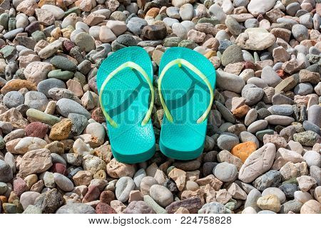 Close up of flip-flops on the colored pebble beach. Summer and vacation concept