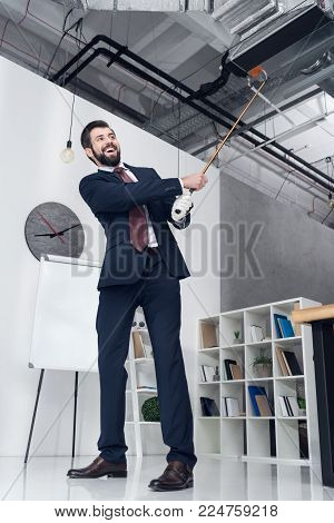low angle view of smiling businessman in suit playing golf in office