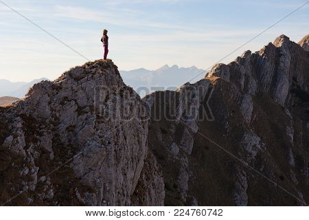 Solitude woman standing on edge of mountain ridge and contemplating beautiful landscape at sunset in Durmitor mountain range, Montenegro. Loneliness concept.
