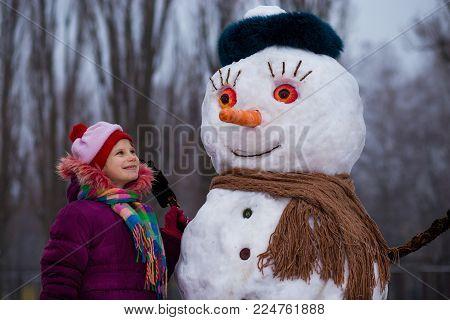 A small cheerful girl near big funny snowman. A cute little girl has fun in winter park, wintertime