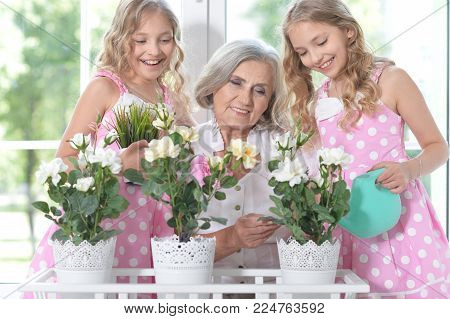 Smiling granny with her granddaughters watering flowers