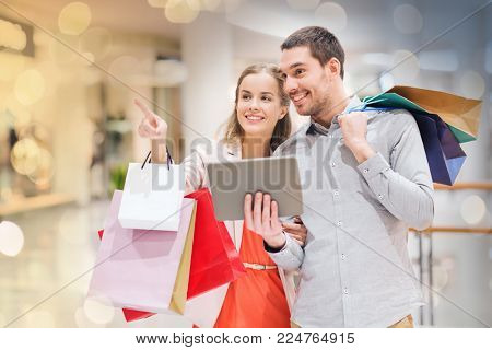 sale, consumerism, technology and people concept - happy young couple with shopping bags and tablet pc computer pointing finger in mall
