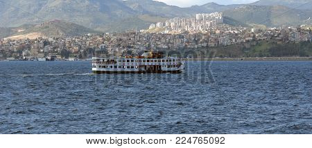 A small ferry on the waves Aegean sea and a picturesque panorama of the Izmir Bay, Turkey.