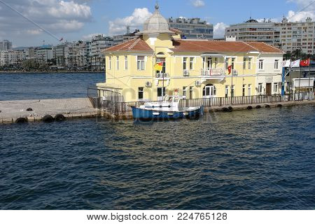 Izmir, Turkey - April 21, 2012: Yellow building of the Passport Ferry Terminal in Izmir Bay. Passport Ferry Terminal, which is one of the historical places to visit in Izmir, Turkey.