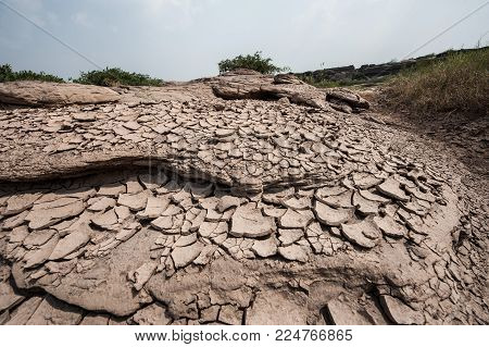 Golden crack earth, dry ground surface, gold brown clay soil texture, drought effect.