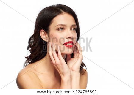 beauty, make up and people concept - happy smiling young woman with red lipstick over white background touching her face
