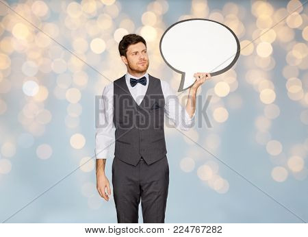 fashion, style and communication concept - concerned man in suit holding blank text bubble banner over holidays lights background