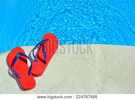 Pair of red flip-flops on the swimming pool.