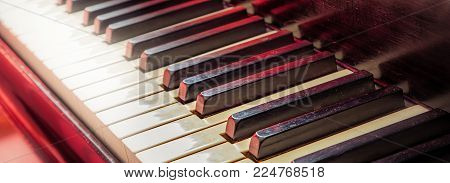 The keys of a piano with a red light in the background.
