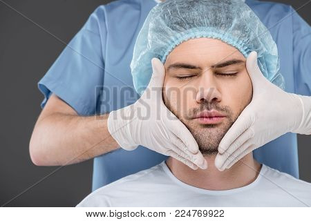 bearded handsome man with closed eyes ready to facelift, isolated on grey