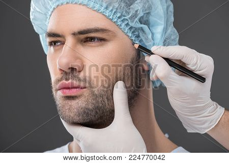 poster of doctor drawing lines for facelifting on man, isolated on grey