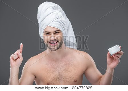 cheerful beardman in towel holding face cream, isolated on grey poster
