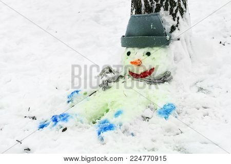 Snowman with a red nose stands in the Park in the snow. Winter fun and games in the fresh air. Funny snowman