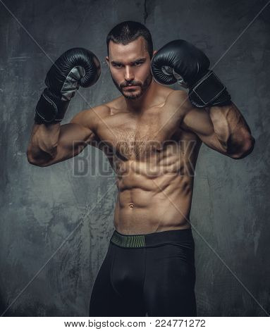 Shirtless aggressive fighter with burning boxer gloves on grey background.