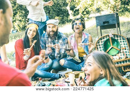 Group of happy friends having fun outdoor cheering at bbq picnic with snacks food drinking red wine - Young people enjoying summer time together at barbecue garden party - Youth friendship concept