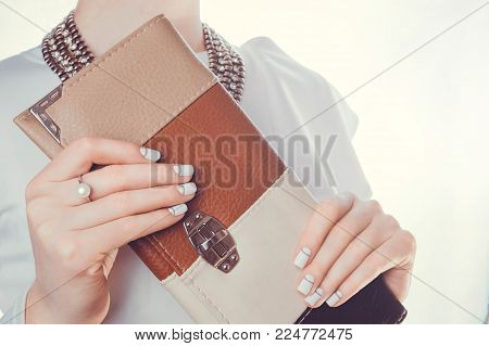 Woman holds a clutch on white background