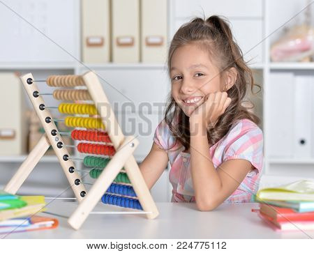 little girl siting at table and counting on abacus