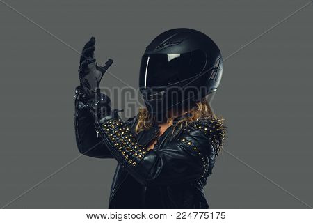 Female in leather clothes, moto gloves and safety helmet on a grey background.