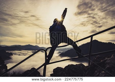 Man with raised hand on top of a mountain, the concept of success, overcoming all difficulties and achieving goals