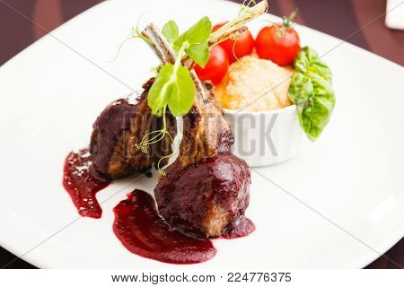 Grilled lamb served with cranberry sauce tomatoes and potato garnish