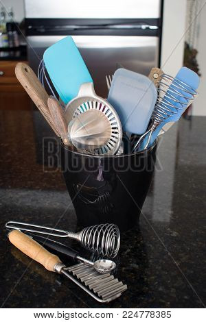 Several kitchen utensils stuffed in a black ceramic container on a black granite counter with some utensils on the counter.