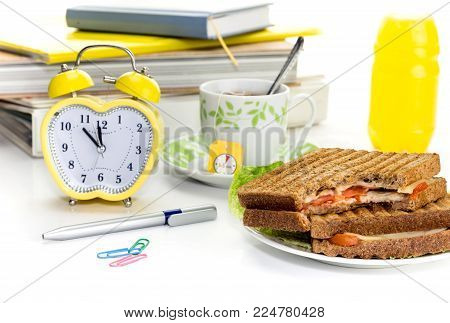 The concept of a lunch break at a school, institute or in the workplace. Toasts on a plate, a cup of tea and a clock on a white background closeup.