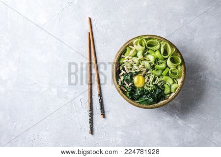 Ceramic bowl with vegetarian green pea noodles with sliced cucumber, celery, spinach, quail egg yolk, pine nuts served with wooden chopsticks. Gray texture background. Top view, space. Healthy eating.