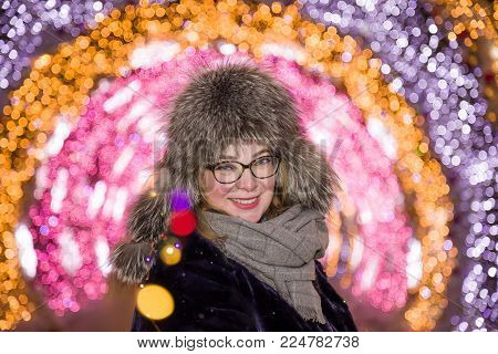 The cheerful joyful smiling girl in a winter fur cap against the background of night festive illumination in the winter in Moscow