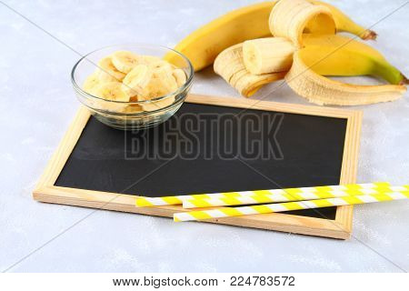An empty chalk board surrounded by a chopped banana on a gray background