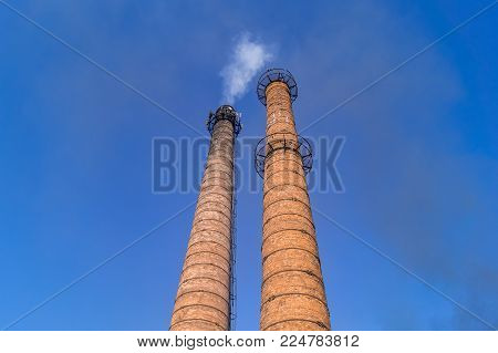 Industrial brick pipes smoke. white smoke on a background of blue sky.