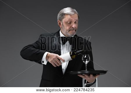 Senior professional waiter in uniform is serving wine isolated on white studio background. concept of good service