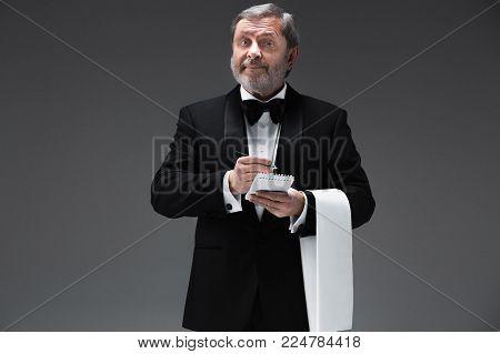 The waiter taking an order wearing a waistcoat in a fancy restaurant