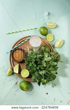 Ingredients for making mojito cocktail. Fresh mint, limes, brown sugar, crashed ice cubes, glass of soda water, cocktail tubes on wooden board over green pin up background. Top view, space