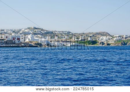 Panoramic vew of Mykonos town (Chora) from the Aegean Sea with its waterfront, white buildings representatives of tourism driven Cycladic architecture, famous windmills and Panagia Paraportiani - the Church of Our Lady.