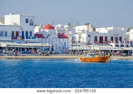 Mykonos, Greece - May 31, 2017:  Mykonos town (Chora) from the Aegean Sea with its waterfront, whitewashed buildings representatives of tourism driven Cycladic architecture, many tourists and a fishing boat