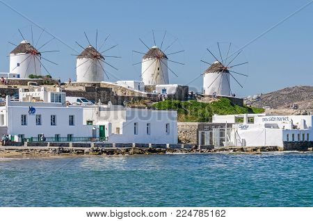 Mykonos, Greece - May 31, 2017: View of Mykonos town (Chora) from the Aegean Sea with its waterfront, white buildings representatives of tourism-driven Cycladic architecture and windmills, built by the Venetians in the 16th century, the main tourist attra
