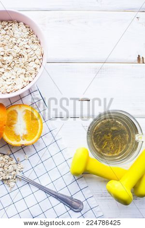 Healthy Breakfast, Sport, Fitness, Diet Concept. A bowl of oatmeal with a glass of green tean and fresh orange, yellow dumbbells, white wood and plaid napkin as a background, top view