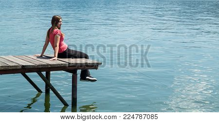 Young woman in red blouse sitting on a pontoon on a river shore.