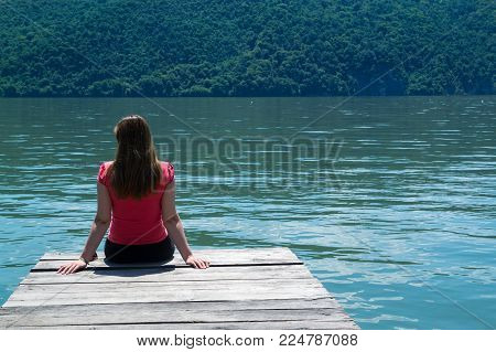 A young woman in red blouse sitting on a pontoon.