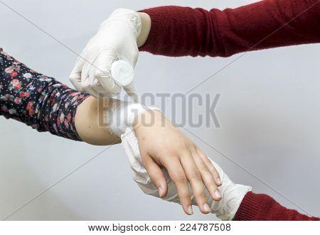Bandaging an injury on the forearm using a white bandage.
