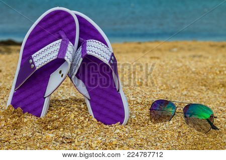 Pair Of Flip Flops And Sunglasses On A Sandy Sea Beach
