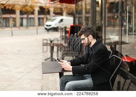 Lucky online poker player sitting at cafe table with tablet enjoying with game in  . Young male person wears black suit and blue shirt.  Concept of real money sites and gaming over the Internet.