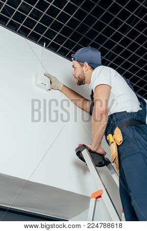 low angle view of young electrician fixing home alarm