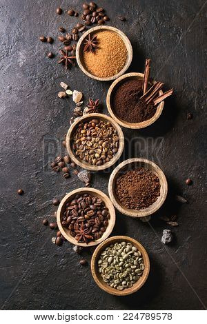 Variety of grounded, instant coffee, different coffee beans, brown sugar, spices in wooden bowls over dark texture background. Top view, space