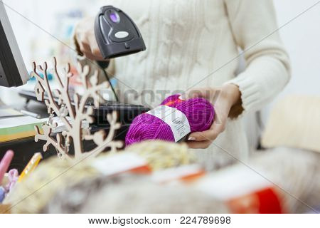 cashier woman register a product price on her system at a white retail store