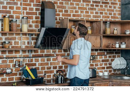young man in eyeglasses holding screwdriver and looking at exhaust hood in kitchen