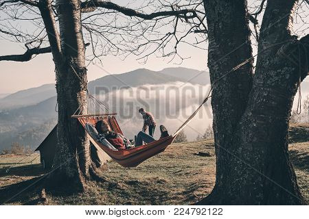 Free your mind! Attractive young woman lying in hammock while camping with her boyfriend