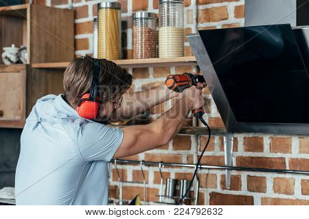 young man in earmuffs drilling kitchen hood with electric drill