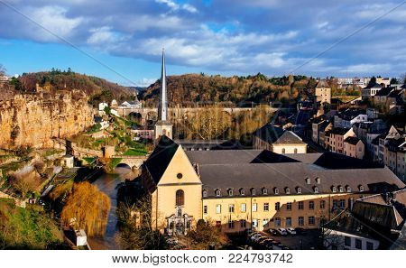 a panoramic view of the Grund Quarter in Luxembourg City, Luxembourg, highlighting the Neumunster Abbey and the Saint-Jean-du-Grund Church in the center