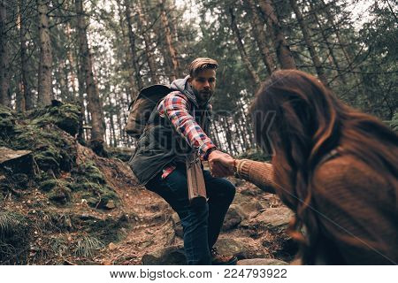 Together we will make it through. Modern young couple holding hands and moving up while hiking together in the woods